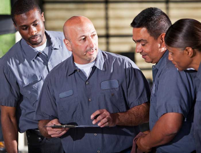 A CDL trainer and three students discussing CDL training.