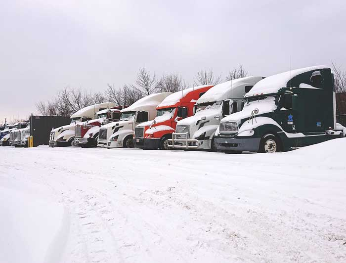 A row of commercial trucks parked in the snow.