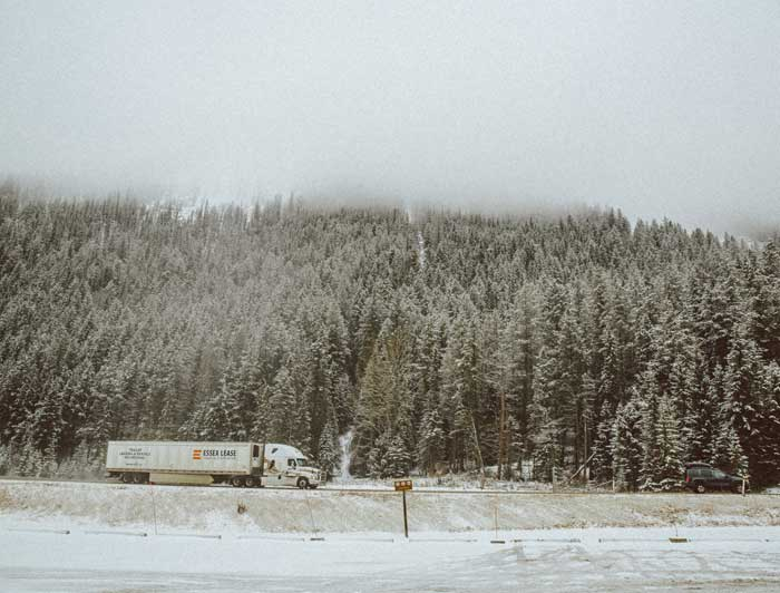 A truck driving down a snowy road.