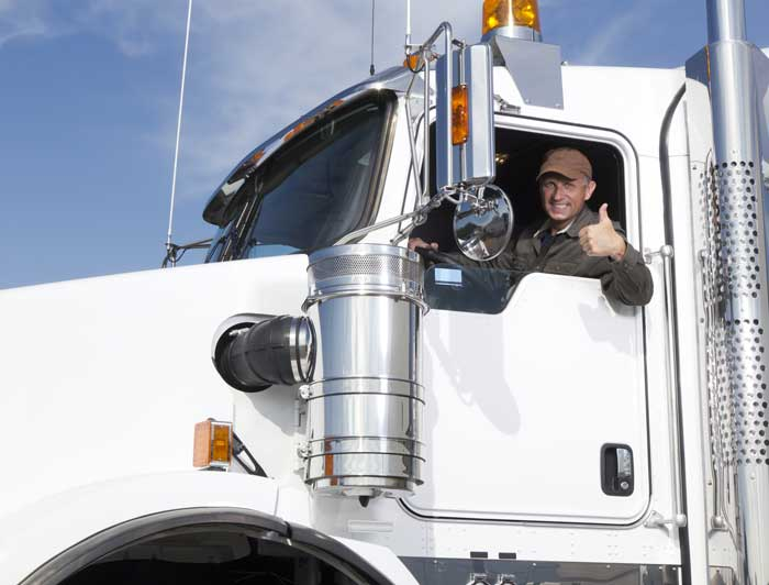 Trucker giving a thumbs up in his truck cab.